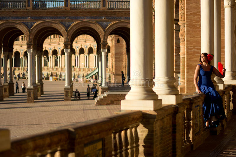 The girl in blue dress and red fan sitting in Plaza de Espana in Seville, Spain. The beautiful Spanish girl in Piazza di Spagna stock photography