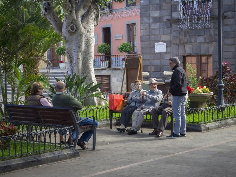 Spain, Canary islands,Garachico, December 19, group of senior lo. Cal people and tourist siting on the banch talking and relaxing in the public park stock image