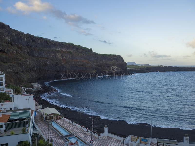 Spain, Canary islands,icod de lod vinos, December 19, 2017, view. On Playa de San Marcos beach with black sand promenade and lava cliffs early morning royalty free stock images