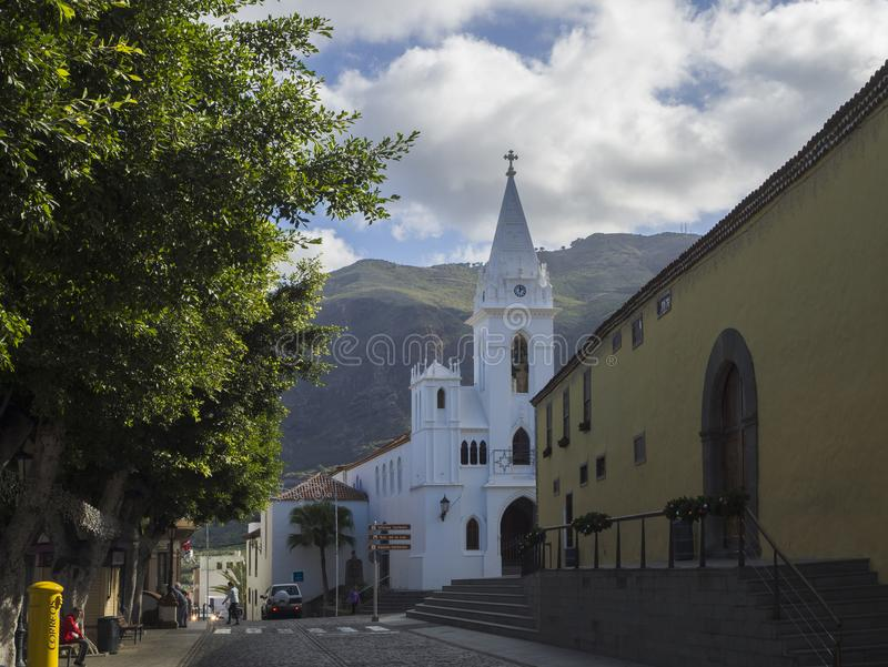 Spain, Canary islands,Tenerife, Los Silos, December 19, 2017: white church and historic buildings in old village with green trees. And hills in background royalty free stock photo
