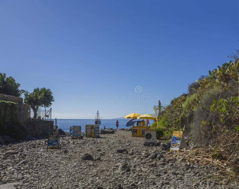 Spain, Canary islands, Tenerife, Masca, December 25, 2017: end o. F macsa valley with stands selling boat trip ticket with view on sea horizon and beach Playa De royalty free stock photography
