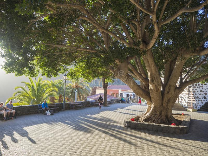 Spain, Canary islands, Tenerife, Masca, December 25, 2017: group. Of tourist resting on bench in pitoresque Masca village with old stone houses, large Ficus royalty free stock photo