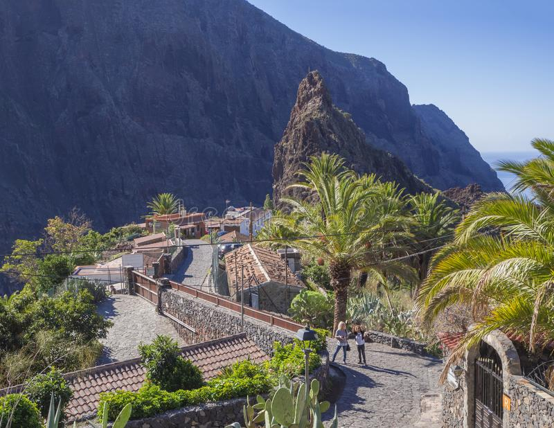 Spain, Canary islands, Tenerife, Masca, December 25, 2017: two w. Oman tourist in pitoresque Masca village with old stone houses, palm tees, beatiful green sharp stock photography