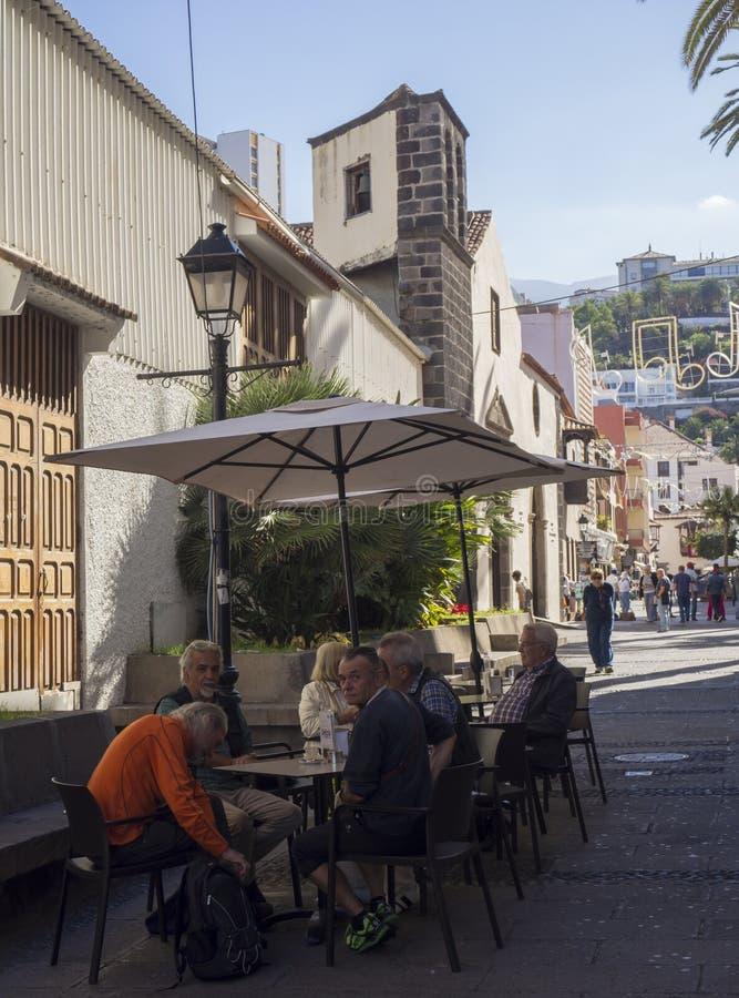 Spain, Canary islands, Tenerife, Puerto de la cruz, December 23, 2017, group of senior tourist people sitting outside on. Restaurant table on street stock images