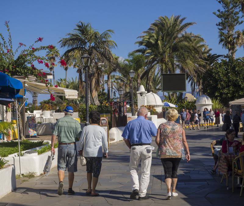 Spain, Canary islands, Tenerife, Puerto de la cruz, December 23, 2017, main promenade with walking senior couples and tourist, pa. Lm trees and blue sky royalty free stock images
