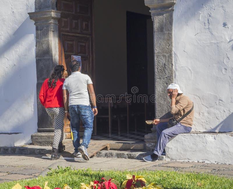 Spain, Canary islands, Tenerife, Puerto de la cruz, December 23, 2017, middle age couple walking the door ofwhite church, men sit. Ting in entrance is begging stock images