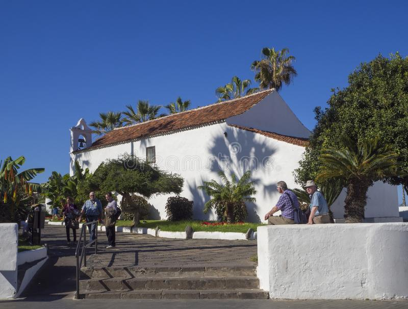 Spain, Canary islands, Tenerife, Puerto de la cruz, December 23, 2017, old small white church and group of walking and relaxing t. Ourist on promenade, palm stock photo