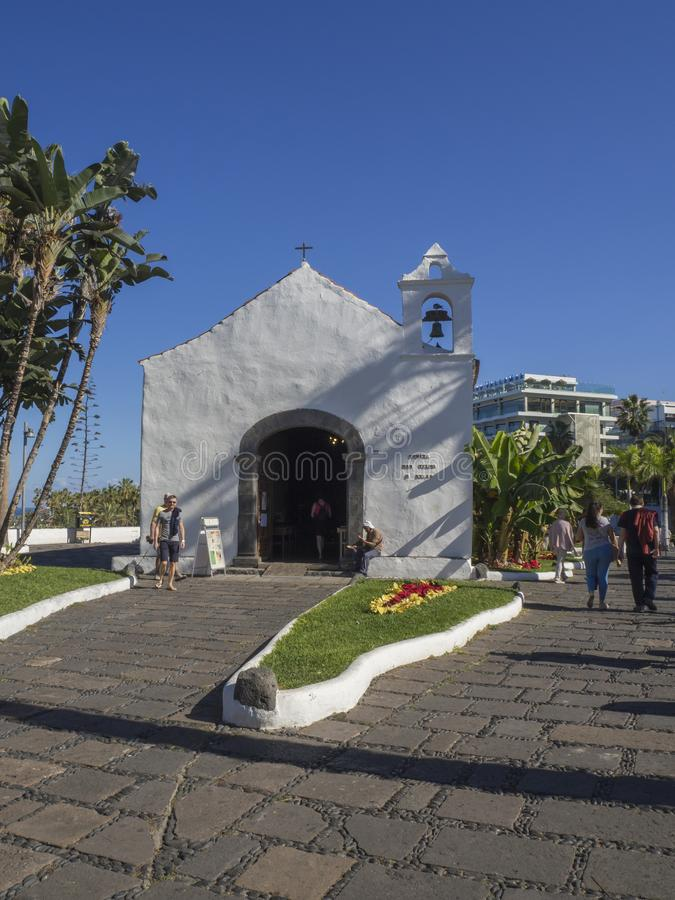 Spain, Canary islands, Tenerife, Puerto de la cruz, December 23, 2017, old small white church and group of walking tourist on pro. Menade, blue sky background stock photography