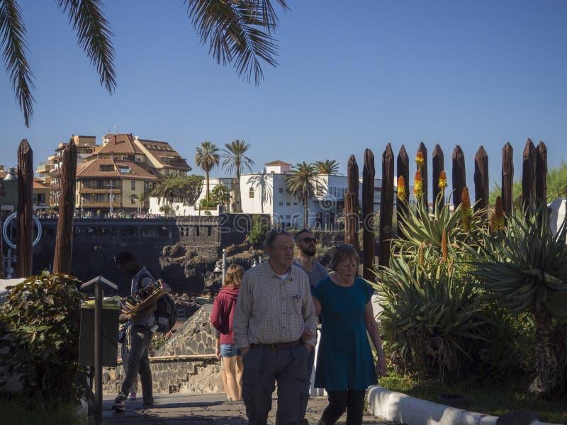 Spain, Canary islands, Tenerife, Puerto de la cruz, December 23, 2017, senior tourist couple walking on main promenade. Wtih tropical flowers street seller stock images
