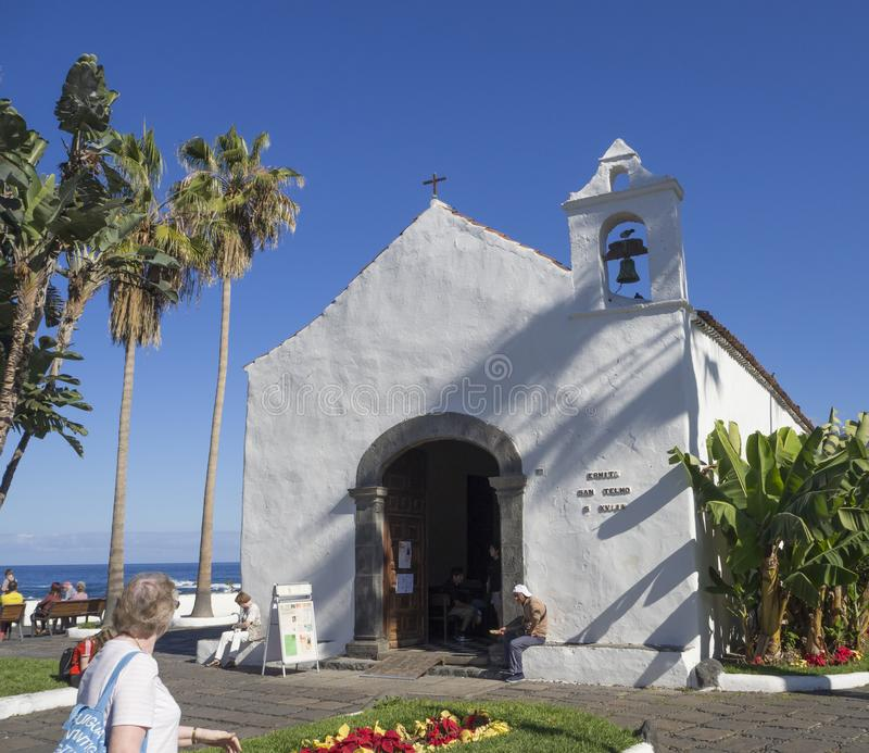 Spain, Canary islands, Tenerife, Puerto de la cruz, December 23, 2017, old small white church, men sitting in entrance portal is. Beging for money and group of stock photos