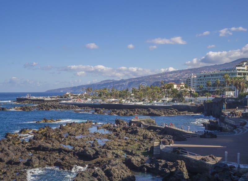 Spain, Canary islands, Tenerife, Puerto de la cruz, December 23, 2017, view on rocky sea pool with big hotel resort buildings pan. Orama of Puerto de la cruz royalty free stock photos