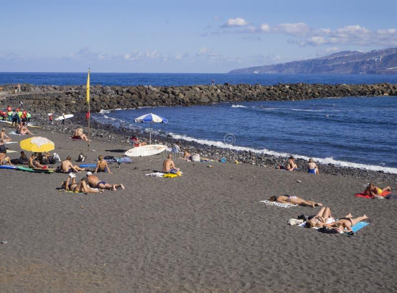 Spain, Canary islands, Tenerife, Puerto de la cruz, December 23, 2017, sunbathing people on send beach in centre of city with blu. E sea horizon, rocks, hills royalty free stock images