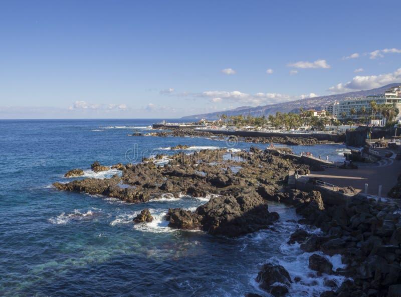 Spain, Canary islands, Tenerife, Puerto de la cruz, December 23, 2017, view on rocky sea pool with big hotel resort buildings pan. Orama of Puerto de la cruz stock photos