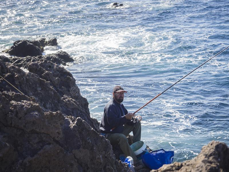 Spain, Canary islands,Tenerife, Punta Teno, December 19, local f. Isherman siting on the lava cllifs holding fishing rod with blue sea background royalty free stock images