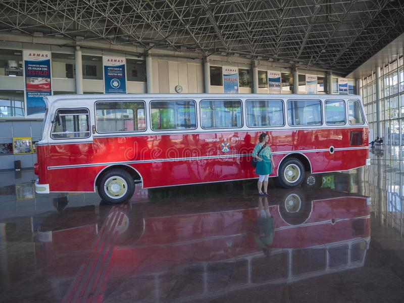 Spain, Canary islands, Tenerife, Santa Cruz de Tenerife, December 27, 2017: woman in blue standing from shiny red bus vintage. Veteran car mercedes placed in royalty free stock photo