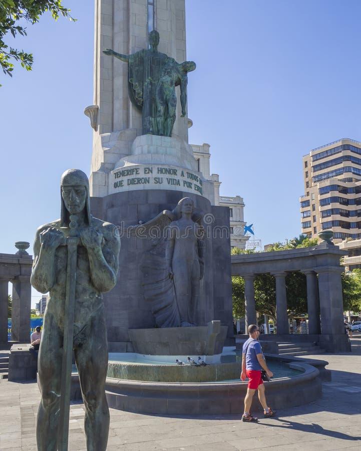 Spain, Canary Islands, Tenerife, Santa Cruz de Tenerife, December 27, 2017: bronze statue of man with sword and monument on main s. Quare Statue at Plaza de la royalty free stock photos