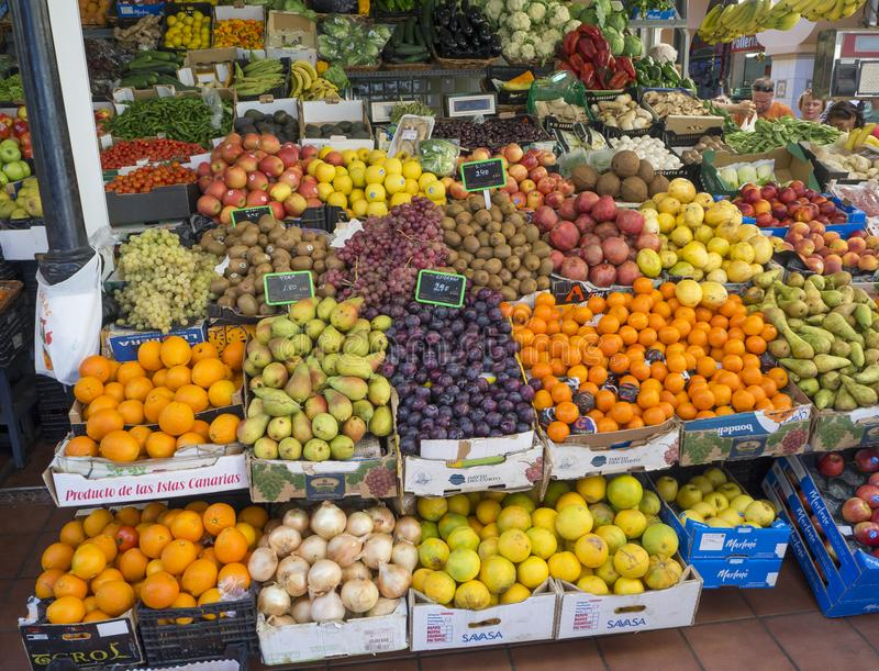 Spain, Canary islands, Tenerife, Santa Cruz de Tenerife, December 27, 2017: fruit and vegetable stand in market hall with. Colorful boxes full of tropical fruit royalty free stock photo