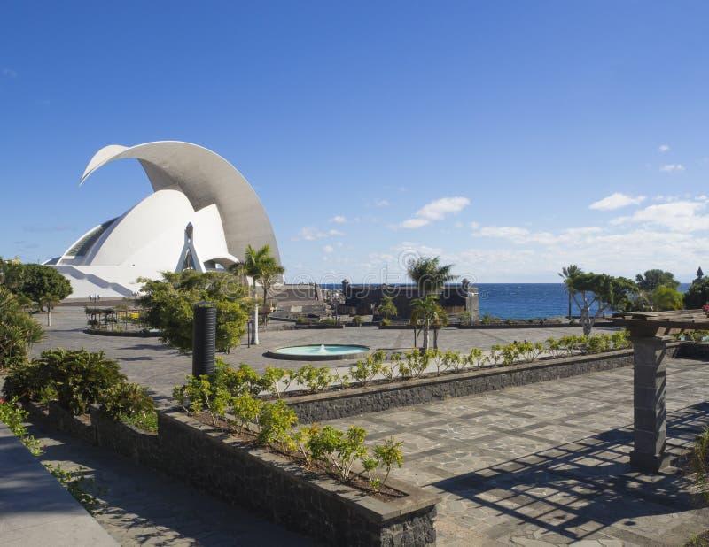 Spain, Canary islands, Tenerife, Santa Cruz de Tenerife, December 27, 2017: seashore promenade with Auditorio de Tenerife, garden. Palm trees and pool in sunny royalty free stock photography