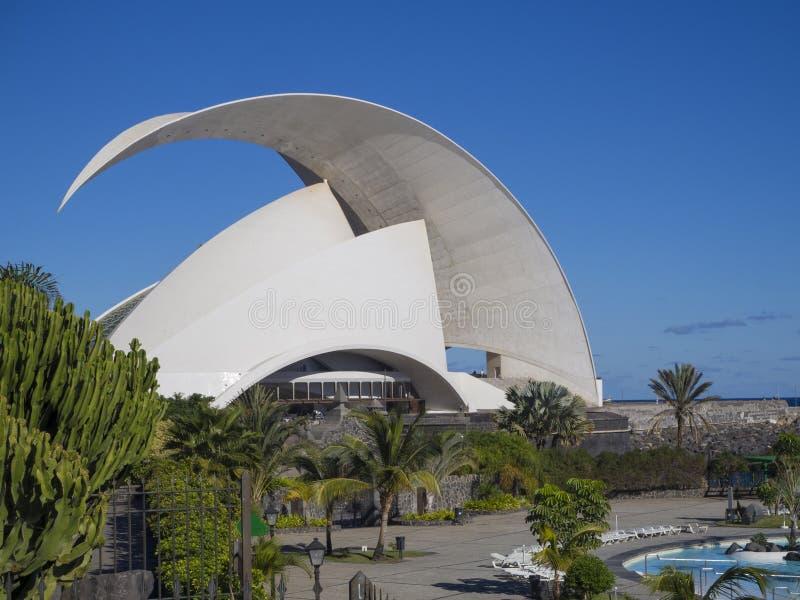 Spain, Canary islands, Tenerife, Santa Cruz de Tenerife, December 27, 2017: Auditorio de Tenerife, palm trees, water pool and blu. E sky background royalty free stock image