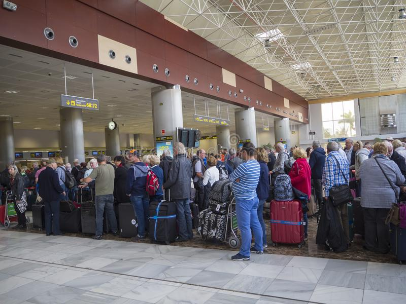 Spain, Canary Islands, Tenerife, Santa Cruz de Tenerife, December 29, 2017: People waiting in long qeue at check-in counter in Te. Nerife airport royalty free stock photography