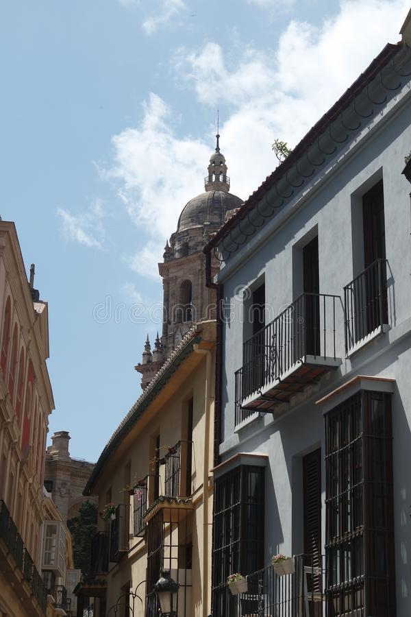 Spain, the city of Malaga. In the distance, from the street, the ornate cathedral on a summers day. Spain, the city of Malaga. The ornate dome and bell tower of royalty free stock photos