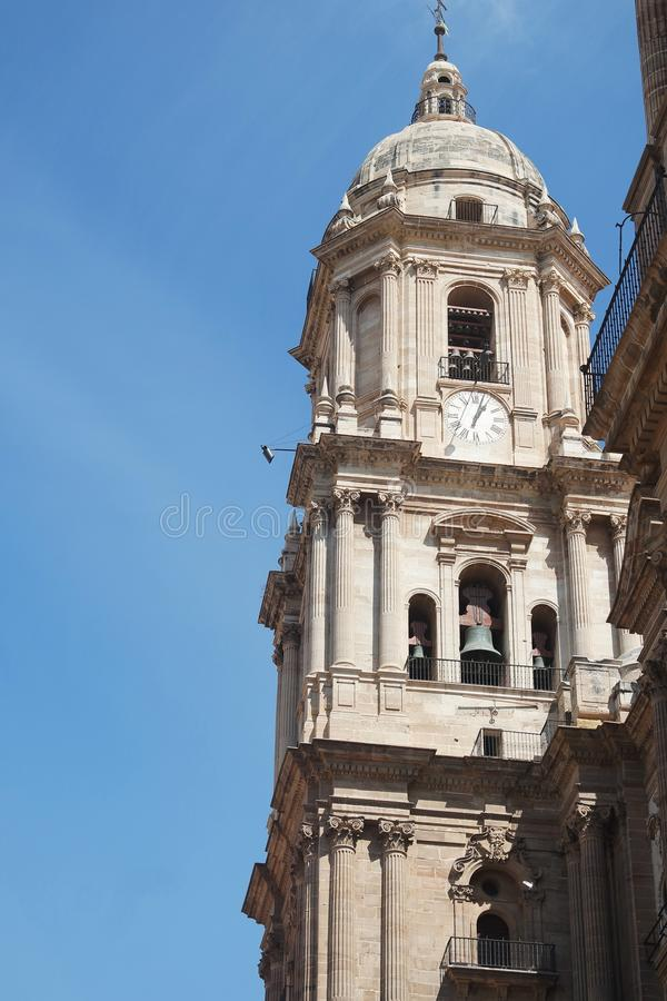 Spain, the city of Malaga. The bell tower of the Cathedral. Spain, the city of Malaga. The ornate cathedral on a summers day. The sculptures and bell tower set stock photography