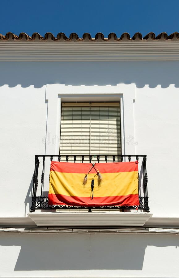 Balcony of a whitewashed house in a southern Spanish town with the flag of Spain with a black ribbon of mourning in memory of thos royalty free stock photo