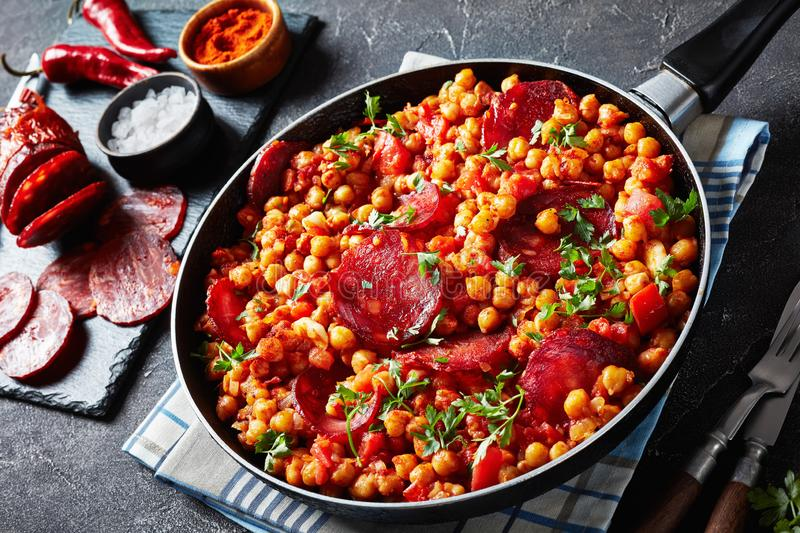 Spain Garbanzos fritos, Chickpea stew with chorizo. Close-up of Garbanzos fritos, stewed Chickpeas with chorizo, ham, tomatoes and spices in a skillet on a stock image