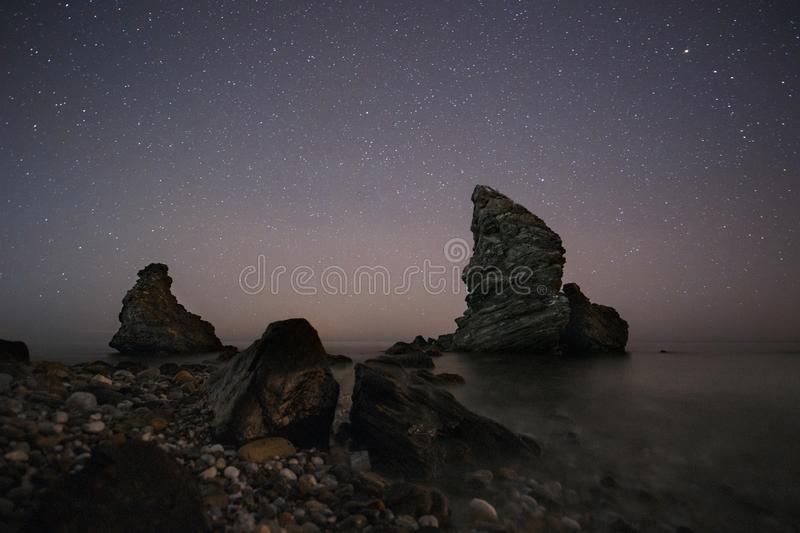 Spain, Malaga, Nerja, Molino de Papel: Starry night on the beach with rocks. And water stock images