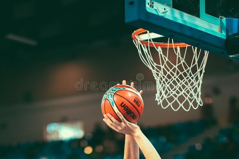 A basketball player put the ball into a basket to score points. royalty free stock photos