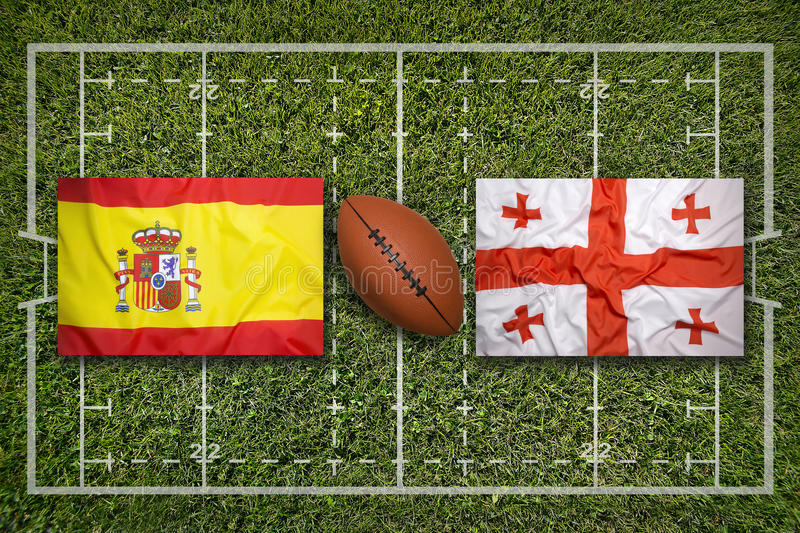 Spain vs. Georgia flags on rugby field. Spain vs. Georgia flags on green rugby field royalty free stock photography
