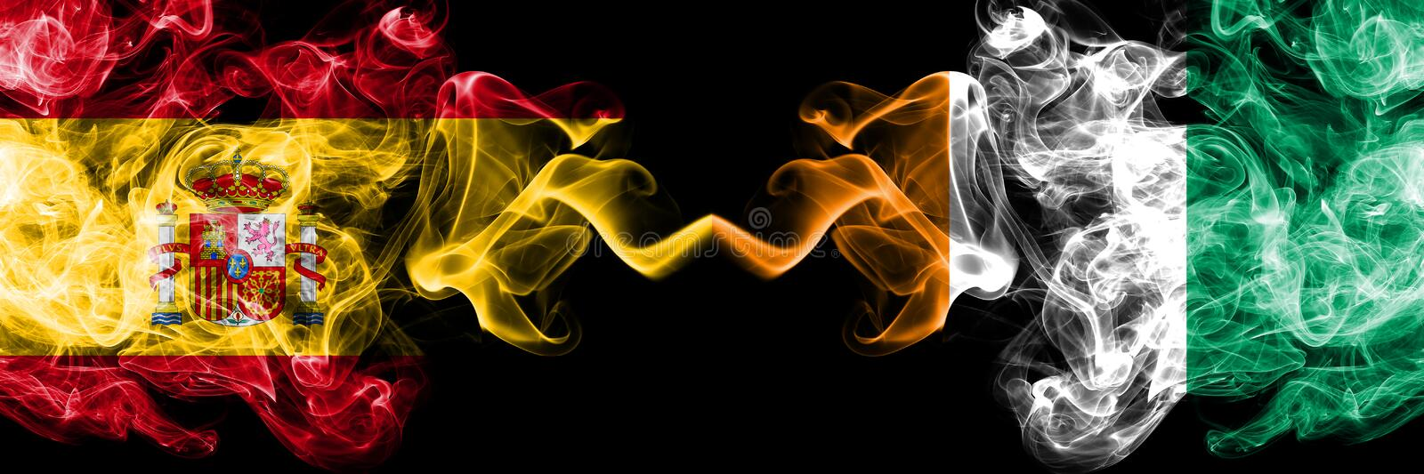 Spain vs Ivory Coast smoky mystic flags placed side by side. Thick colored silky smokes flag of Spanish and Ivory Coast.  royalty free stock images