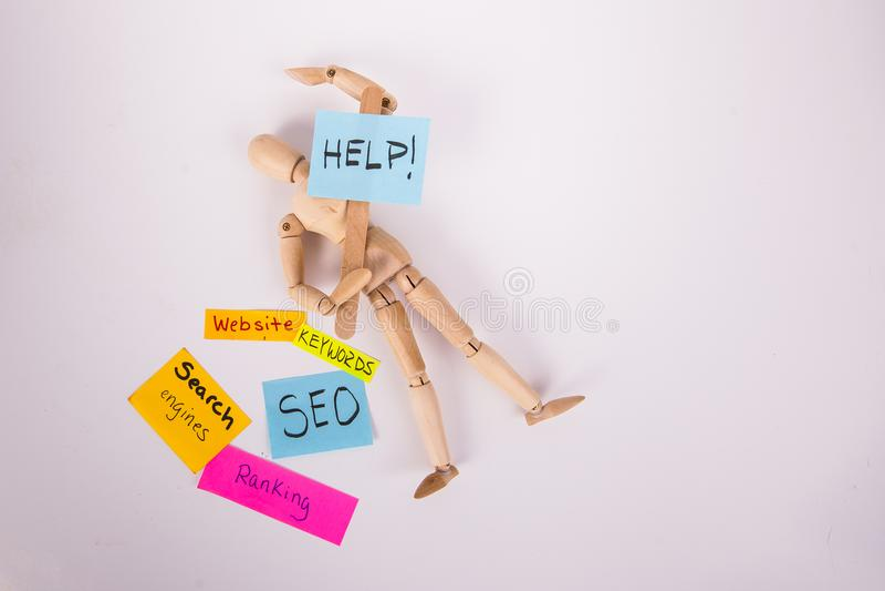 Spajająca Drewniana lala kłaść w dół trzymać pomoc palika znaka notatek SEO rankingu stron internetowych kleistych słowa kluczowe zdjęcia stock