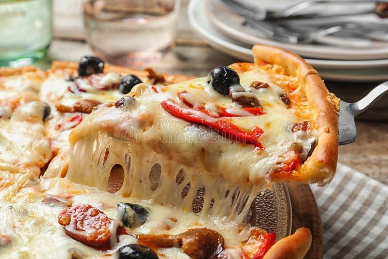 Spali con la fetta di pizza calda deliziosa sopra la tavola fotografia stock