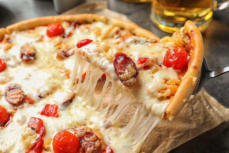 Spali con la fetta di pizza calda deliziosa sopra la tavola, fotografie stock libere da diritti