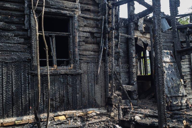 Spalony do węgli drewnianego domu Czarny dom w ogniu fotografia stock