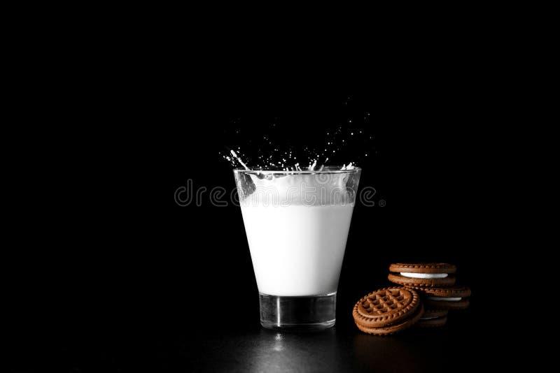 Spalsh in glas melk en chocoladekoekjes op zwarte achtergrond royalty-vrije stock afbeeldingen