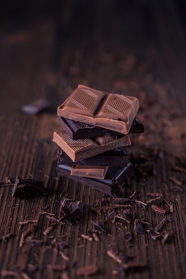 Spalte der Dunkler oder bitterer oder Milchschokolade auf einem hölzernen Hintergrund stockfotografie