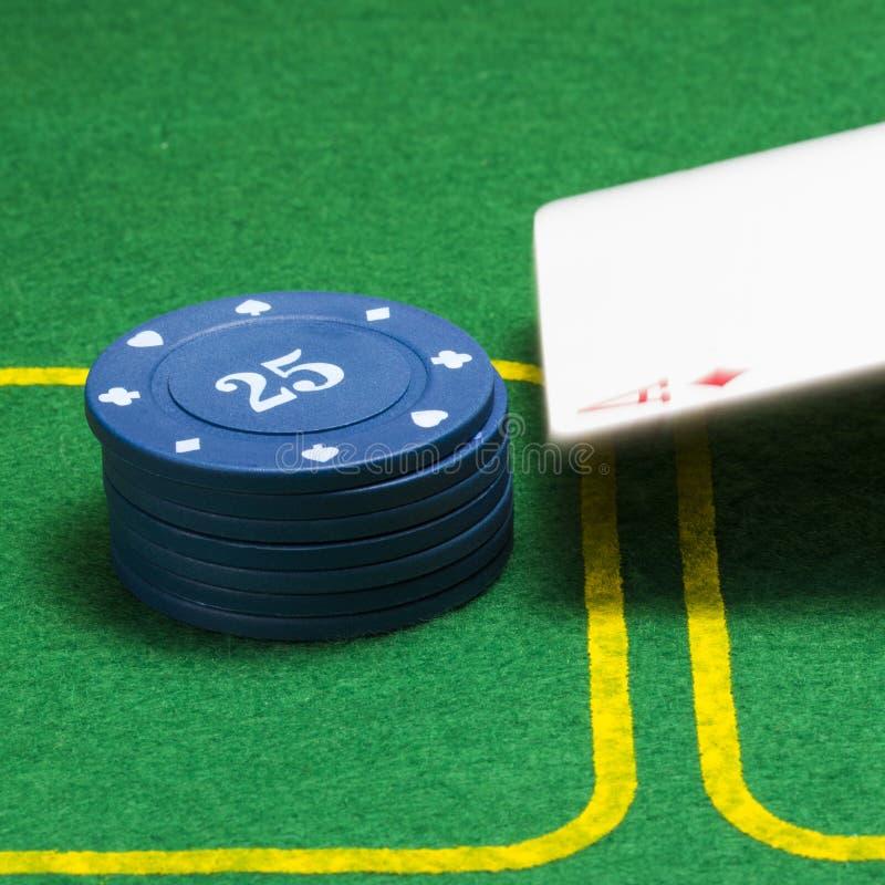 Spalte von blauen Pokerchips und ein fallendes Pikass stockbilder