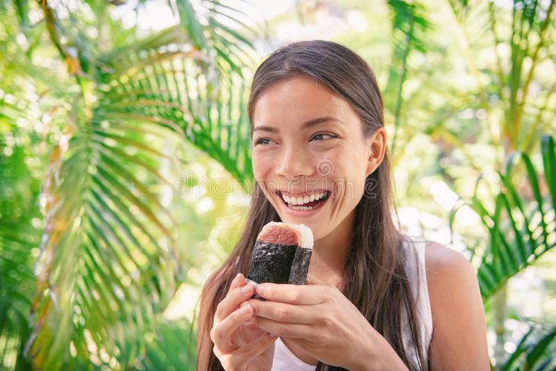 Spam musubi rice ball sandwich Asian woman tourist eating japanese snack food typical of hawaiian market royalty free stock photo
