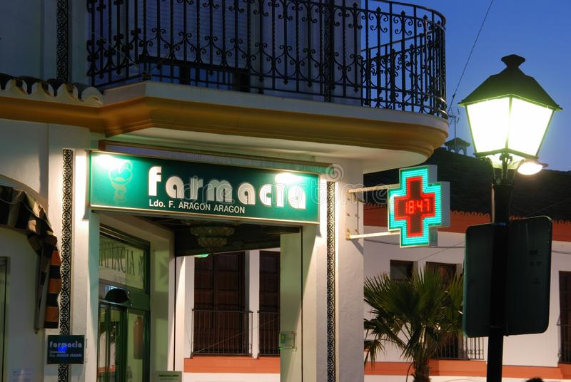 Pharmacy shop at dusk, La Cala de Mijas, Spain. Front view of a pharmacy shop in the town centre at dusk, La Cala de Mijas, Costa del Sol, Malaga Province royalty free stock photos