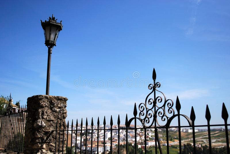 Ornate ironwork fence with views over part of the town and countryside, Ronda, Spain. stock image