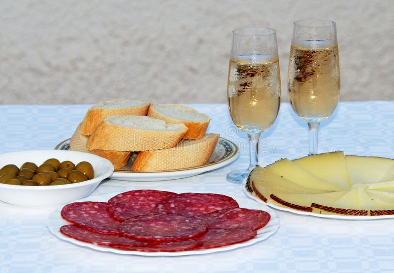 Cold Spanish tapas selection. A selection of Spanish tapas including Manchego cheese, green olives and salami with two glasses of fino sherry, Andalusia, Spain stock image