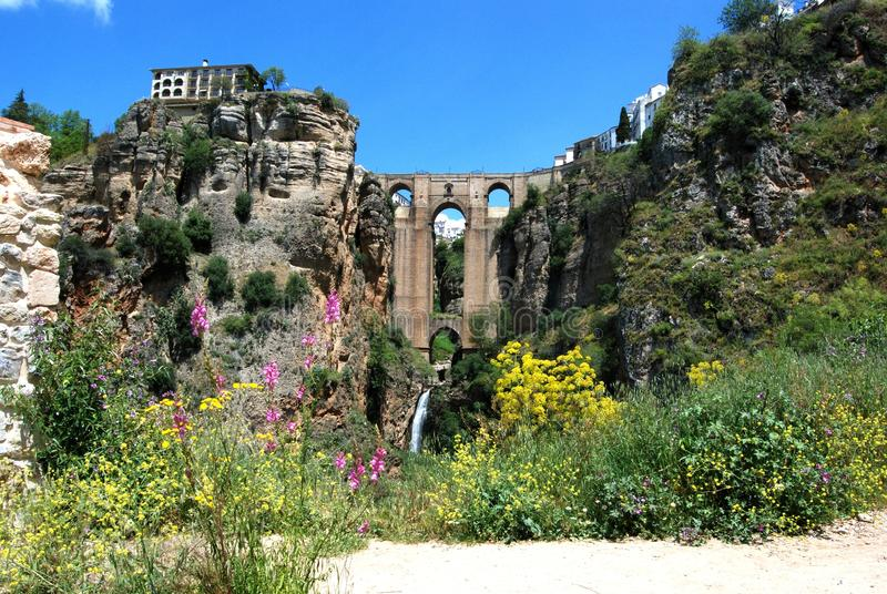 View of the New Bridge and ravine with pretty Spring flowers in the foreground, Ronda, Spain. stock photos