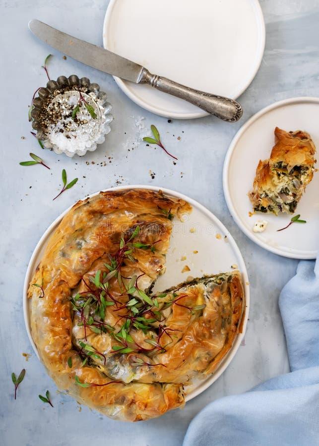 Spanakopita greco della torta su fondo blu-chiaro Idee e ricette per la torta degli spinaci del vegano o del vegetariano dalla pa immagine stock libera da diritti