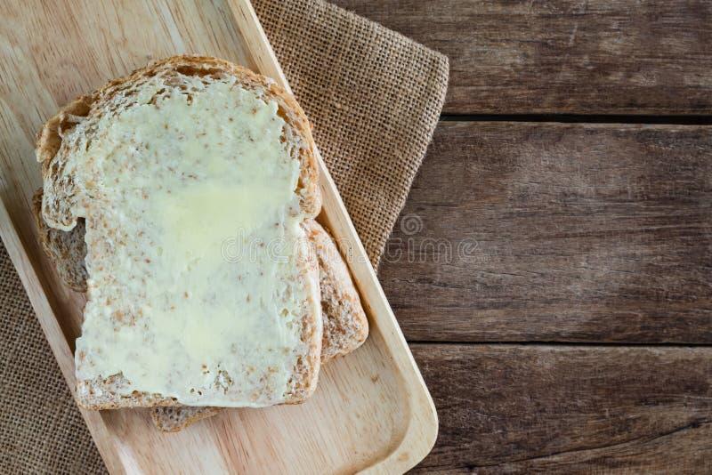 Spanda il pancarrè del grano intero della fetta impilato burro sul piatto di legno sulla tavola di legno immagine stock libera da diritti