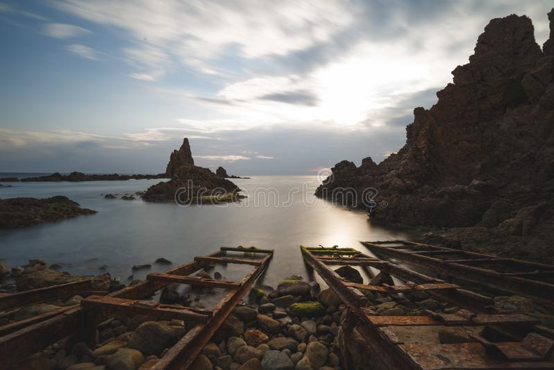 Spanien AlmerÃa, Cabo de Gata, sirenrev Arrecife de las sirenas - lång exponering på solnedgång, havet och siden- effekt på  arkivfoto