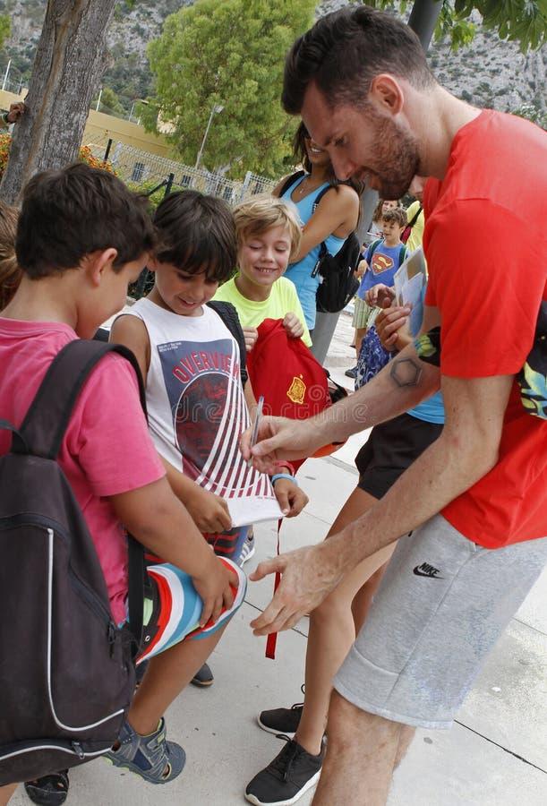 Spanien basketspelare och gamlaNBA, Rudy Fernandez undertecknande autografer till några barn på en sommaruniversitetsområde arkivfoto