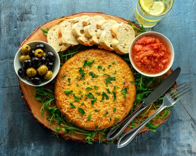 Spanische klassische Tortilla mit Kartoffeln, Oliven, Tomaten, rucola, Brot und Kräutern lizenzfreies stockfoto
