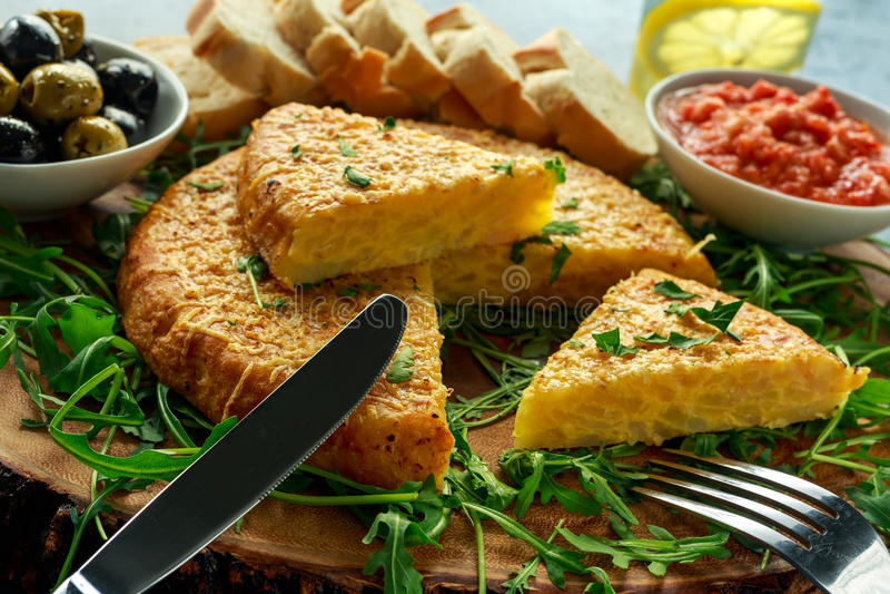 Spanische klassische Tortilla mit Kartoffeln, Oliven, Tomaten, rucola, Brot und Kräutern lizenzfreies stockbild